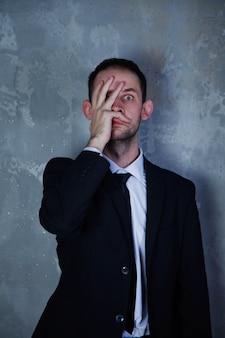 スーツを着て落ち込んでいる若い男は、灰色のテクスチャ背景に恐怖と恐怖を描いています。人のジェスチャーは恐怖とヒステリーについて話します、それは彼にとって不快です。人間の感情の概念。コピースペース