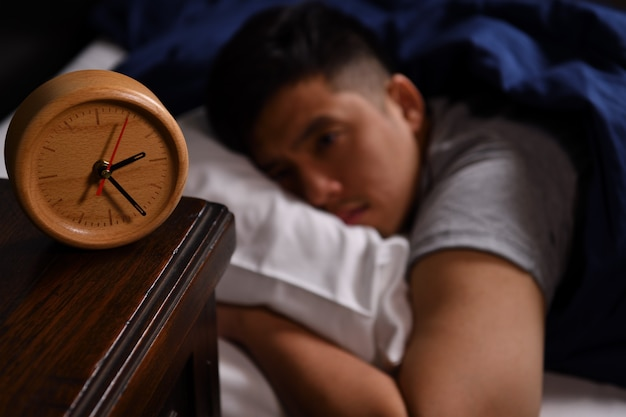 A depressed young man suffering from insomnia lying in bed. selective focus on alarm clock