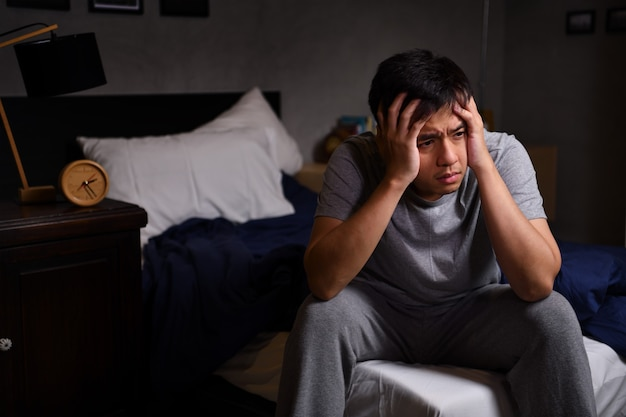 Depressed young man suffering from insomnia sitting in bed