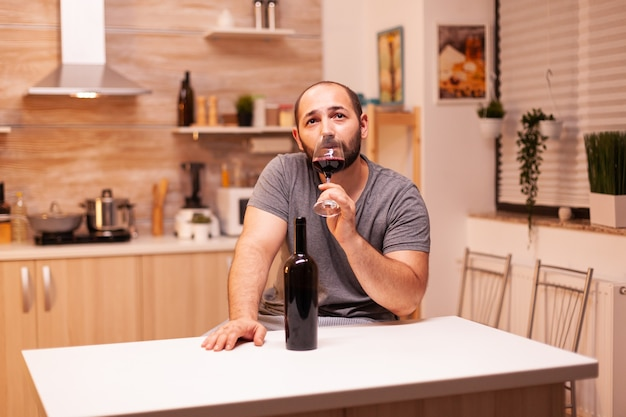 テーブルに座ってキッチンでワインテイスティングを持っているアルコール中毒の落ち込んでいる若い男。アルコール依存症の問題で疲れ果てた不幸な人の病気と不安感。