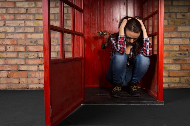 落ち込んでいる若い女性は、携帯電話が耳の横にぶら下がっているときに、頭を手に持って電話ブースに座って床にしゃがみ込んだ