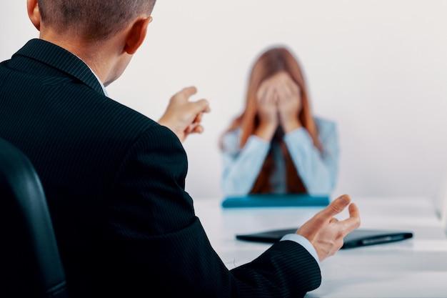 Подавленная молодая женщина во время разговора с начальником, который указывает на ее ошибки