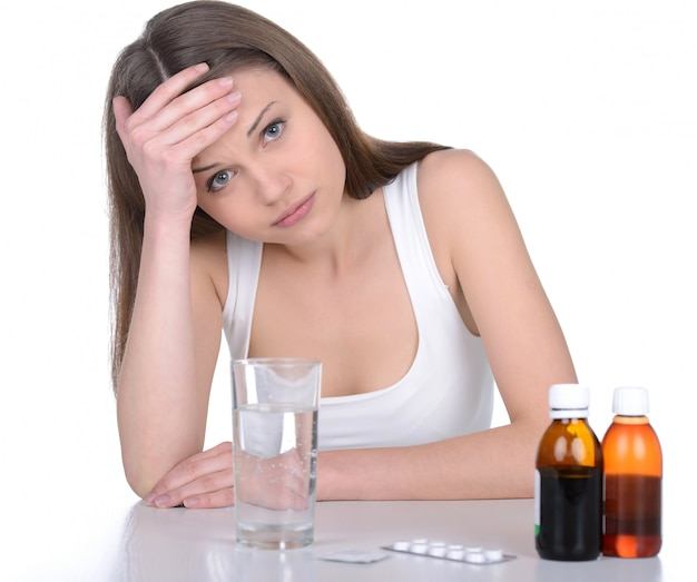 Depressed young woman holding medicines.