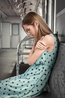 電車の中で落ち込んでいる若い女性