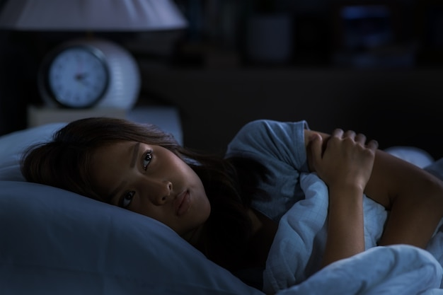 Depressed young woman lying in bed cannot sleep from insomnia