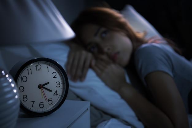 침대에 누워 우울한 젊은 여성은 불면증으로 잠을 잘 수 없습니다. 알람 시계에 선택적 초점