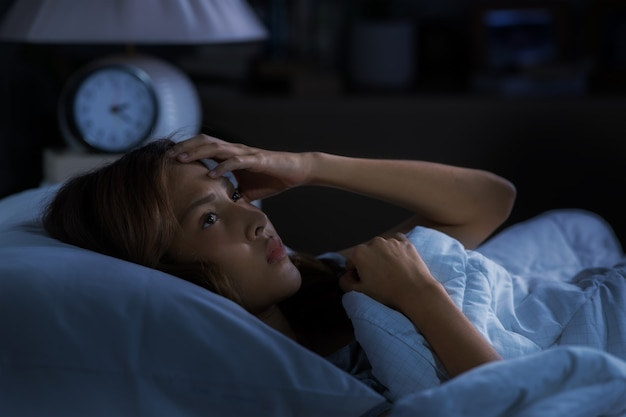 침대에 누워 우울한 젊은 여성이 불면증으로 잠을 잘 수 없습니다