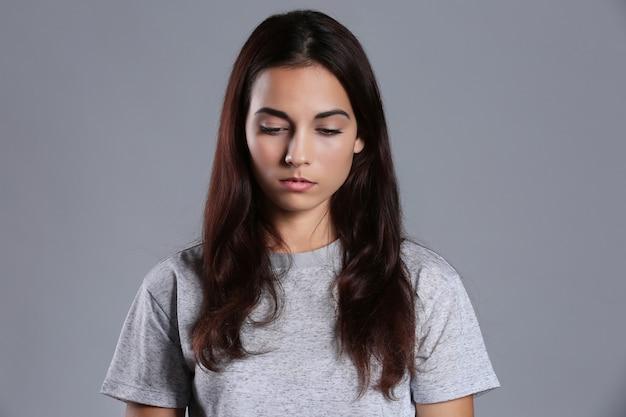 Подавленная молодая женщина на цветном фоне Premium Фотографии