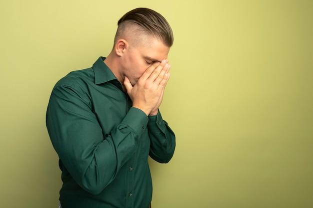 Deprimente giovane uomo bello in camicia verde che copre il viso con le braccia stressate e nervose