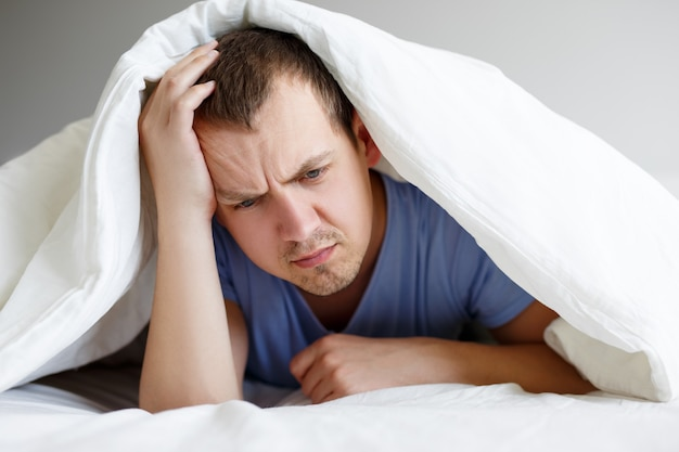 うつ病の概念-毛布の下でベッドに横たわっている悲しいまたは疲れた男