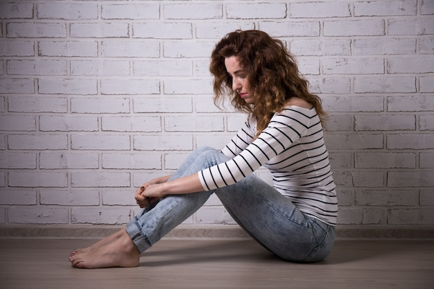 Depression - lonely sad woman sitting on the floor over white brick wall