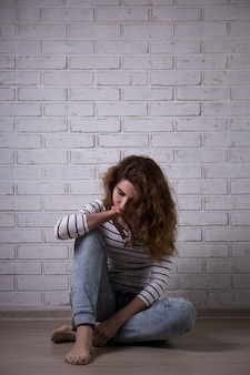 Depression - unhappy woman sitting on the floor over white brick wall