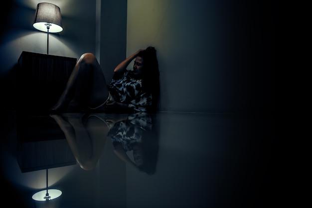 暗い部屋で一人でうつ病の女性。メンタルヘルスの問題、ptsdは心的外傷後ストレス障害です。