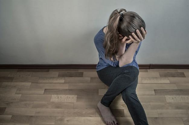 うつ病の女性が床に座っている。悲しい、絶望的な、抑圧された女の子。