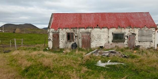 荒れた草と庭に壊れたごみが残っている放棄された荒廃農村の住居