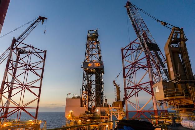 夕暮れの空を持つ海上油掘削リグのderickとクレーンの眺め。