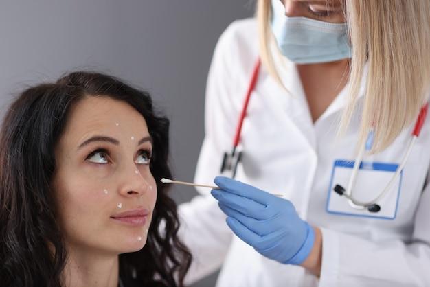 Дерматолог наносит на лицо пациента белый крем. концепция лица омолаживающие процедуры