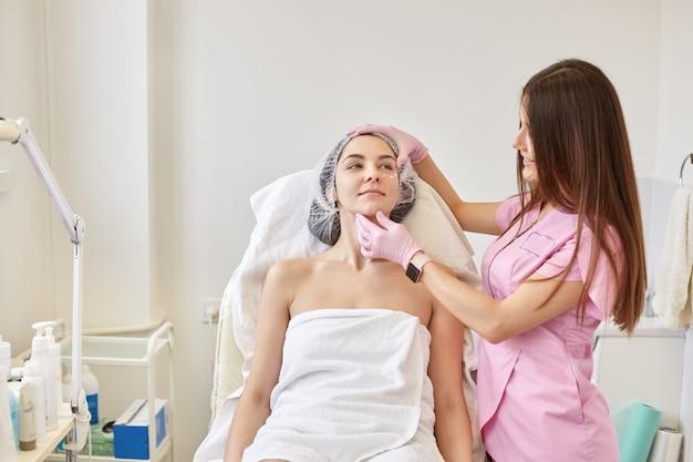 皮膚科医が女性の目の周りにローションを適用します。