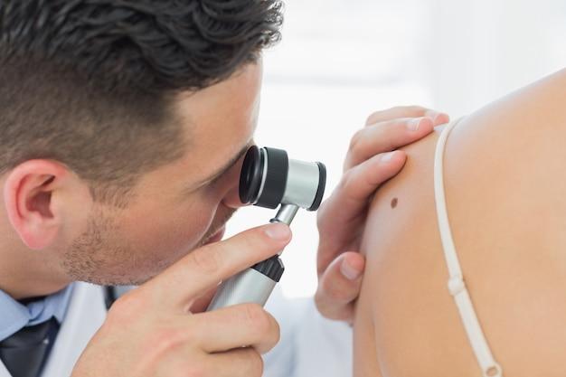 Dermatologist checking mole on woman