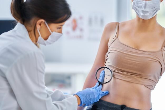 Дерматолог осматривает свою пациентку в маске