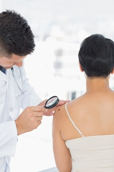 Dermatologist examining mole on woman with magnifying glass in clinic