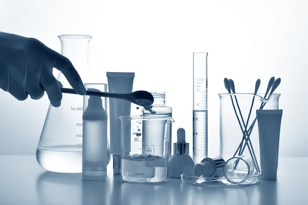 Dermatologist formulating and mixing pharmaceutical skincare, cosmetic bottle containers and scientific glassware, research and develop beauty product concept.