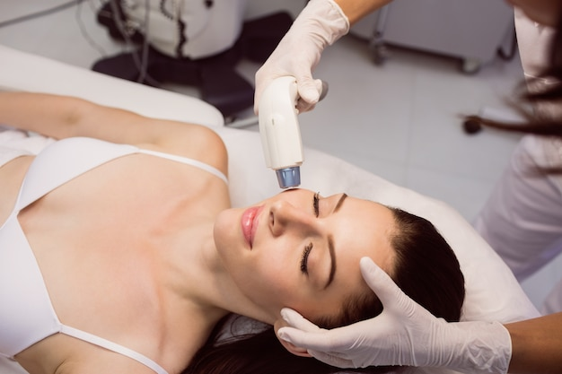 Dermatologist giving facial massage through soniclifting