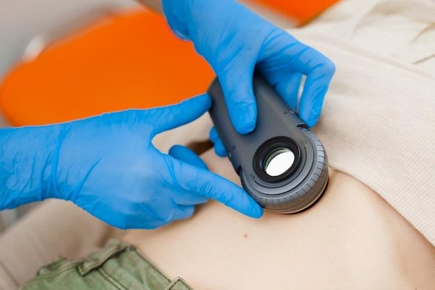 피부과 의사는 피부 경을 사용하여 검사를합니다. 의사와 상담하십시오. 젊어지게하는 절차
