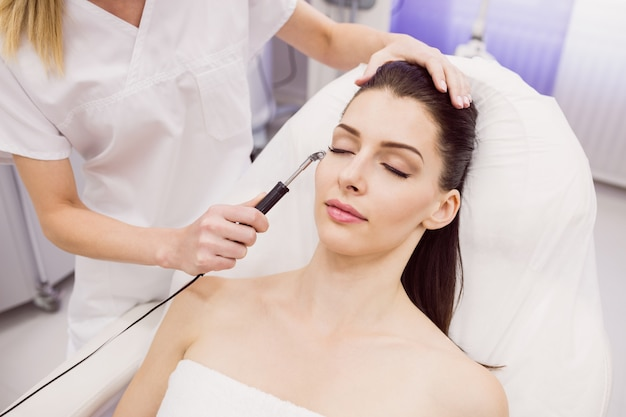 皮膚科医が患者にレーザー脱毛を行う