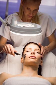 皮膚科医が患者にレーザー脱毛を行う 無料写真