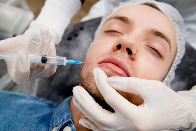 Дерматолог делает уколы в губы мужчины, чтобы сделать их больше и сложнее.