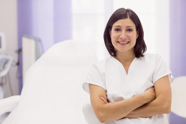 Дерматолог, стоя со скрещенными руками в клинике