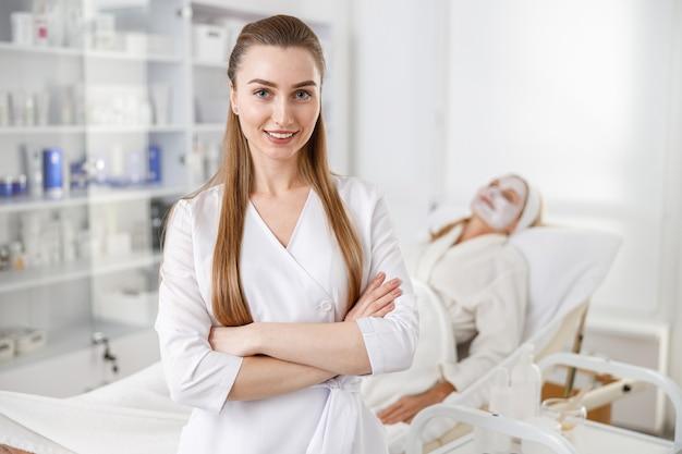 Дерматолог со скрещенными руками стоит рядом с пациентом, лежащим на кушетке во время медицинской процедуры.