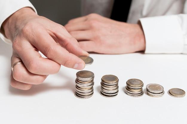 Нисходящие груды монет и человек