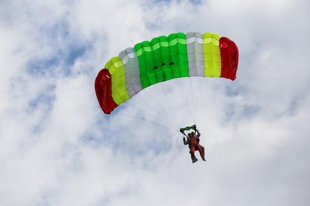 Descending tandem paratroopers on color parachute