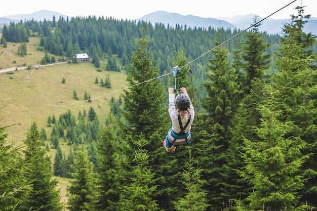 金属ケーブルで山から降りる。ジップラインは本質的に極端な種類の楽しみです Premium写真