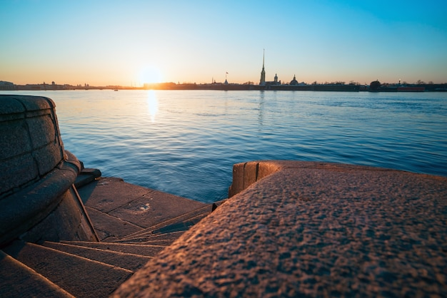 Descent to the neva granite steps, view of the peter and paul fortress, st. petersburg.