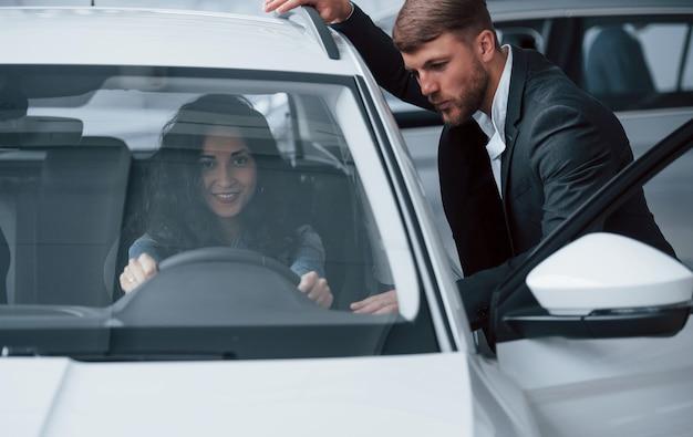Descrivi come ti senti al riguardo. cliente femminile e uomo d'affari barbuto elegante moderno nel salone dell'automobile