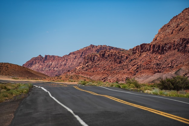 雲とアスファルトとオレンジ色の岩の空と日没の旅行の概念米国の風景で砂漠の高速道路...