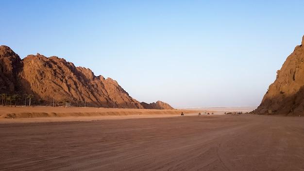 エジプトの砂漠。岩だらけの砂丘。青い空と山々を背景に砂漠のatvで一人の観光客が紅海に向かって歩いています。砂漠の風景。