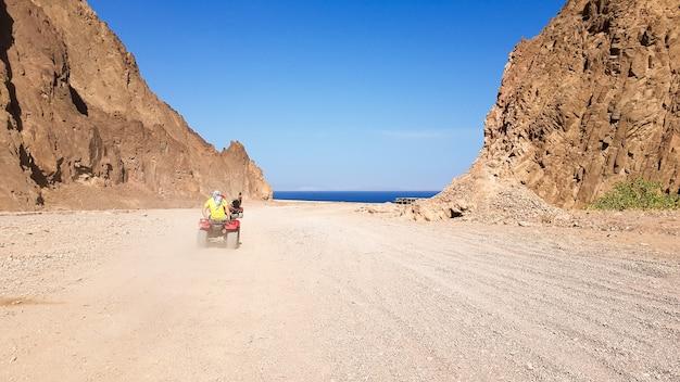 Пустыня в египте. скалистые песчаные холмы. одинокий турист на квадроцикле по пустыне на фоне голубого неба и гор идет к красному морю. пейзаж в пустыне.