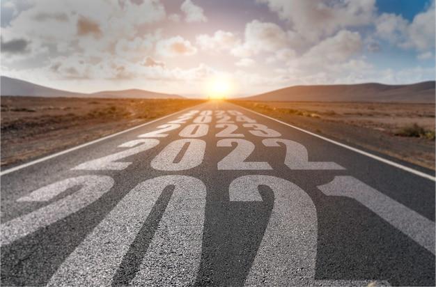 2021年、2022年、2023年、2024年、2025年の砂漠の風景が道路に白く塗られています。