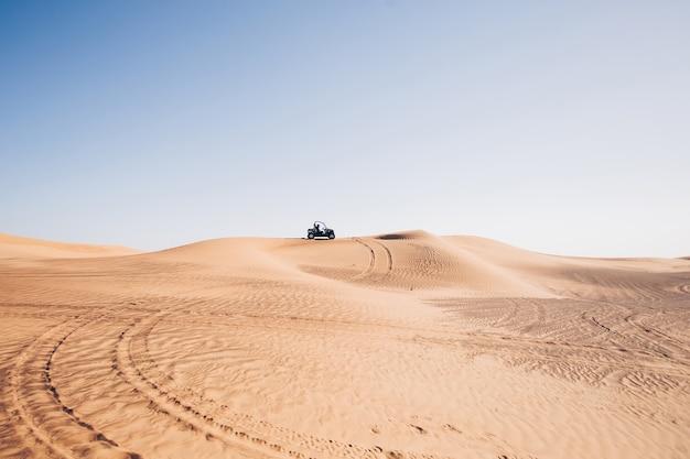 Uae 두바이 알 아위르 언덕에 바퀴 흔적과 버기 쿼드 바이크가 있는 사막 풍경