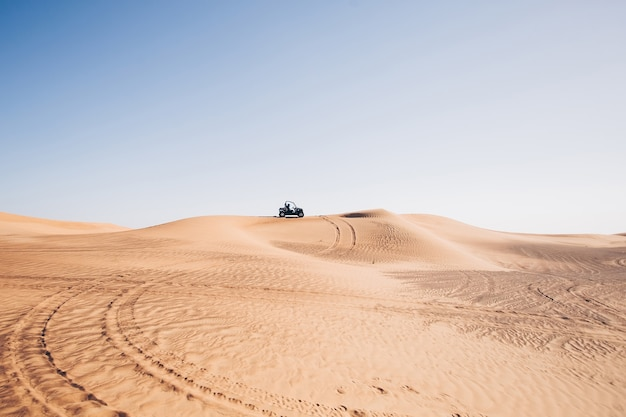 Desert landscape with wheel traces and buggy quad bike on hill at al awir, dubai, uae