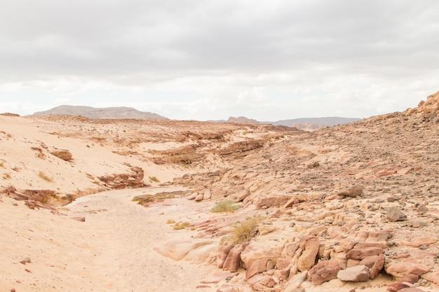 Пустыня, красные горы, скалы и облачное небо. египет, цветной каньон.