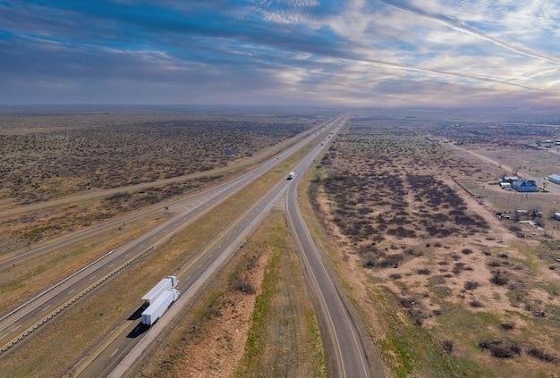 米国ニューメキシコ州サンジョン近郊の砂漠の風景に囲まれた新しい2車線道路の砂漠道路空中