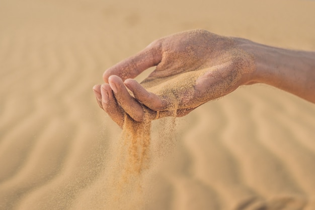 砂漠、男の手の指から砂を吹き飛ばす