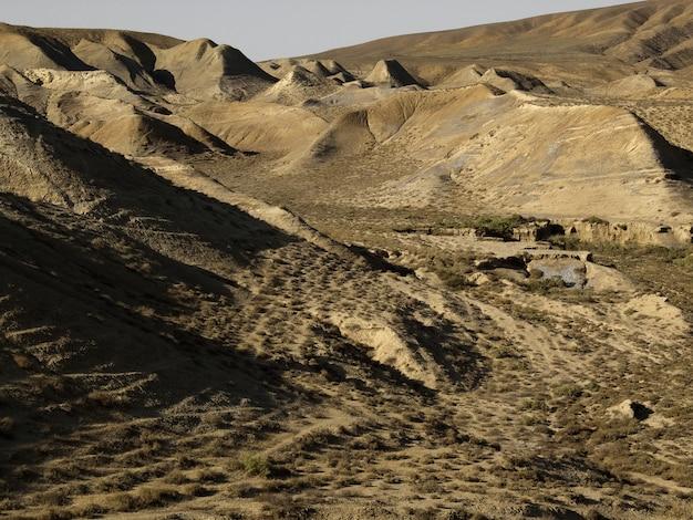 孤独で静かな砂漠の場所で、青い空を背景に茶色の砂