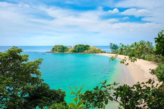 黄色いきれいな砂、ターコイズブルーの海、雲と青い空と人けのないビーチ