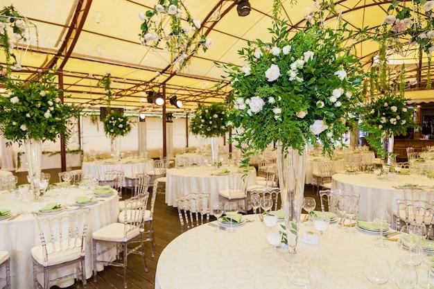 白いバラ、緑の葉、キャンドル、花の花束で結婚式のお祝いのデザインと装飾の装飾
